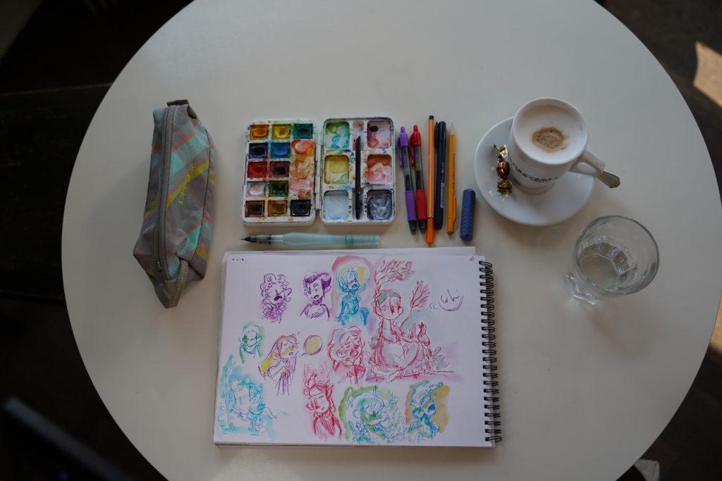 Kit de dessin: une table, des crayons et un café.